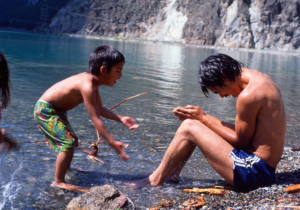 Father playing by the water with his son.