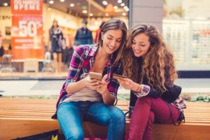 Young women in the mall using credit card for online shopping